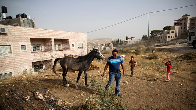 Homes are seen on either side of an Israeli military barrier in the Palestinian village of Sur Baher