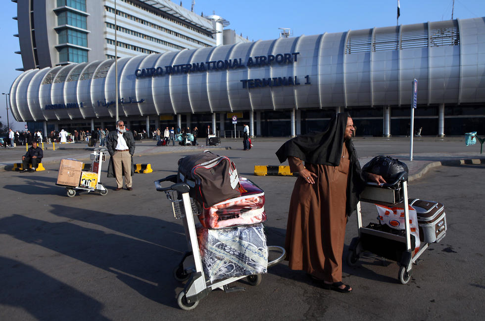 גבר ערבי עומד עם המזוודה שלו מחוץ לנמל תעופה בקהיר (צילום: EPA)