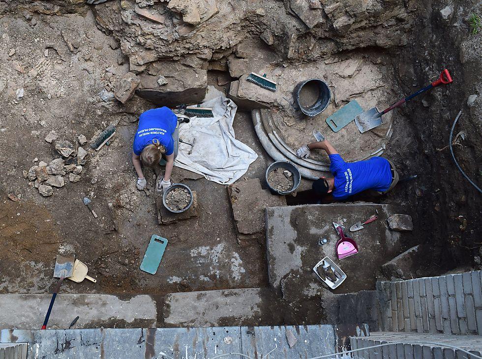 צווות החפירה חושף את בסיס אחד העמודים הענקיים שתמכו את תקרת בית הכנסת בווילנה (צילום: יוחנן (ג'ון) זליגמן, רשות העתיקות)