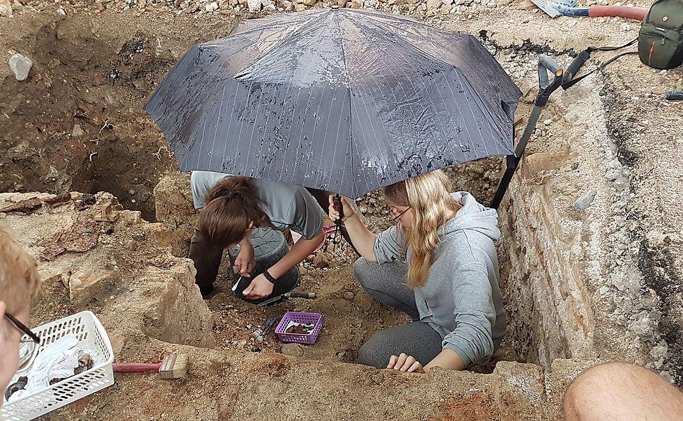חברות צוות החפירה בבית הכנסת הגדול בוילנה חושפות ספר תפילה ששרד את השואה (צילום: יוחנן (ג'ון) זליגמן, רשות העתיקות)