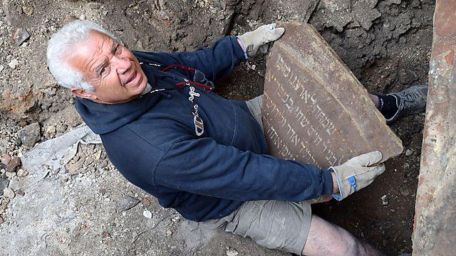 חבר צוות החפירה מחזיק את אחד משברי הכתובת שנתגלתה (צילום: יוחנן (ג'ון) זליגמן, רשות העתיקות)
