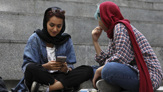 An Iranian woman uses her cell phone on the steps outside of a shopping mall in northern Tehran, July 2, 2019