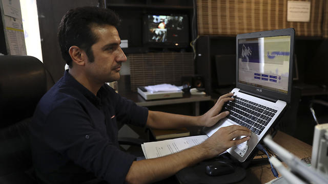 An internet cafe manager works on his computer in Tehran, July 25, 2019