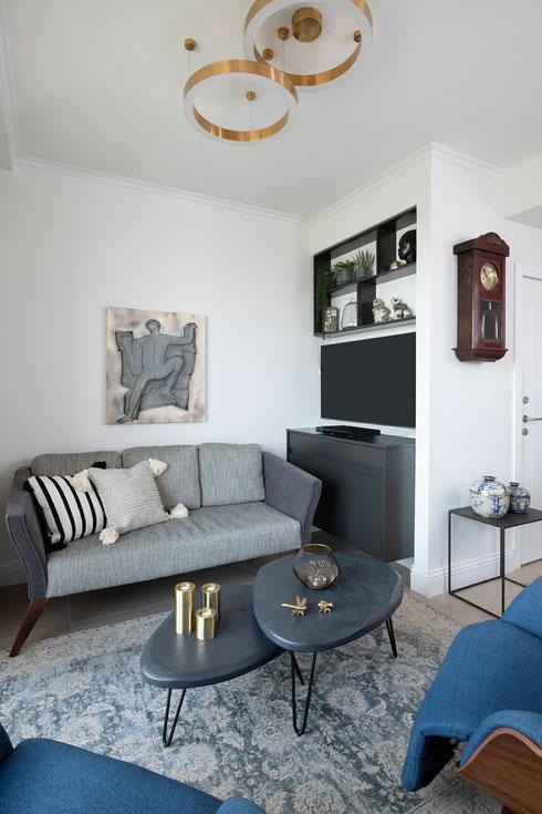 מבט מהמטבח אל הסלון והכניסה. הטלוויזיה תלויה על זרוע, כך שניתן לשלוף אותה אל מול הכורסאות (צילום: הגר דופלט)