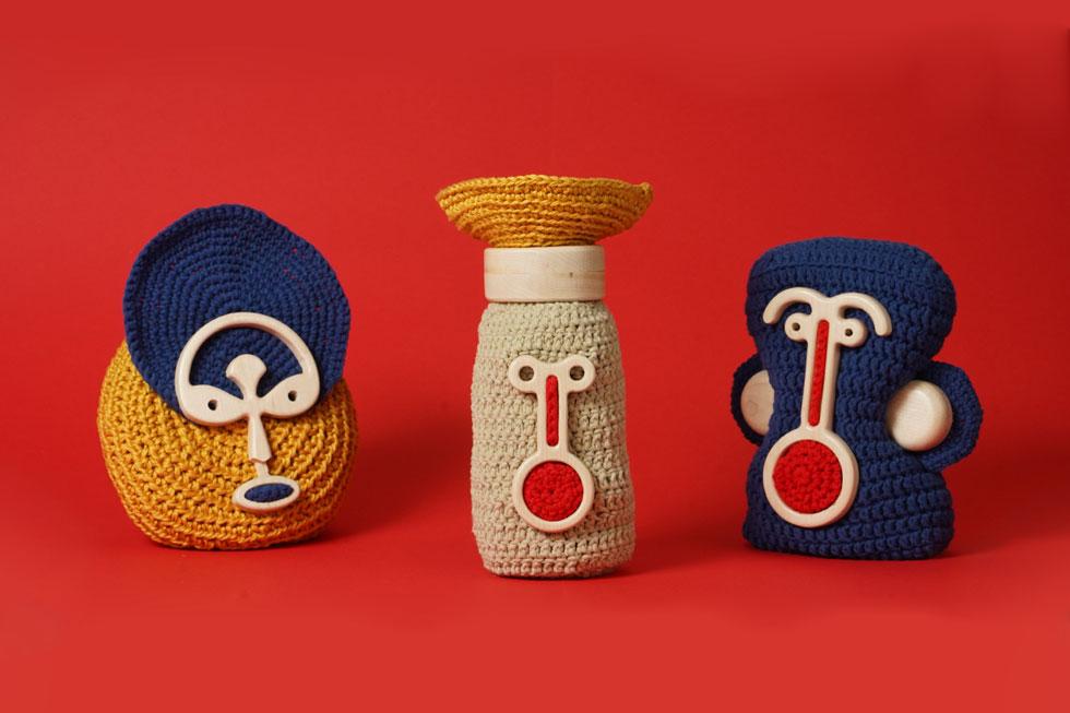 הפרויקט של שיר חנית: בובות שסורגות מבקשות מקלט מאריתריאה, ולהן נוספים תווי פנים מעץ (עיצוב: שיר חנית)
