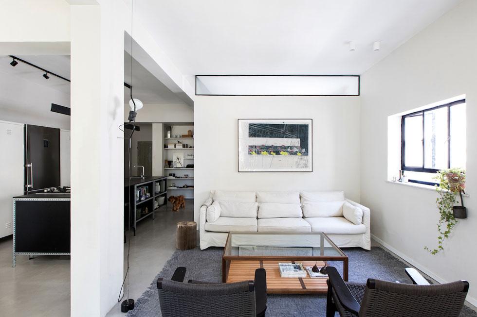 מבט מכיוון המרפסת דרך המטבח עד לכניסה. בגב הספה קיר חדר הרחצה שבלב הדירה, שבמרומיו נקבע חלון צר - פס אור נוסף לסלון ולמטבח (צילום: שירן כרמל)
