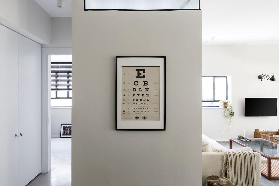 """במסדרון המוביל לחדר האורחים (משמאל) יש ארון גדול. בזכות פס האור העליון בקיר חדר הרחצה, """"הקיר נראה בלילה כמו גוף תאורה תלת ממדי""""   (צילום: שירן כרמל)"""