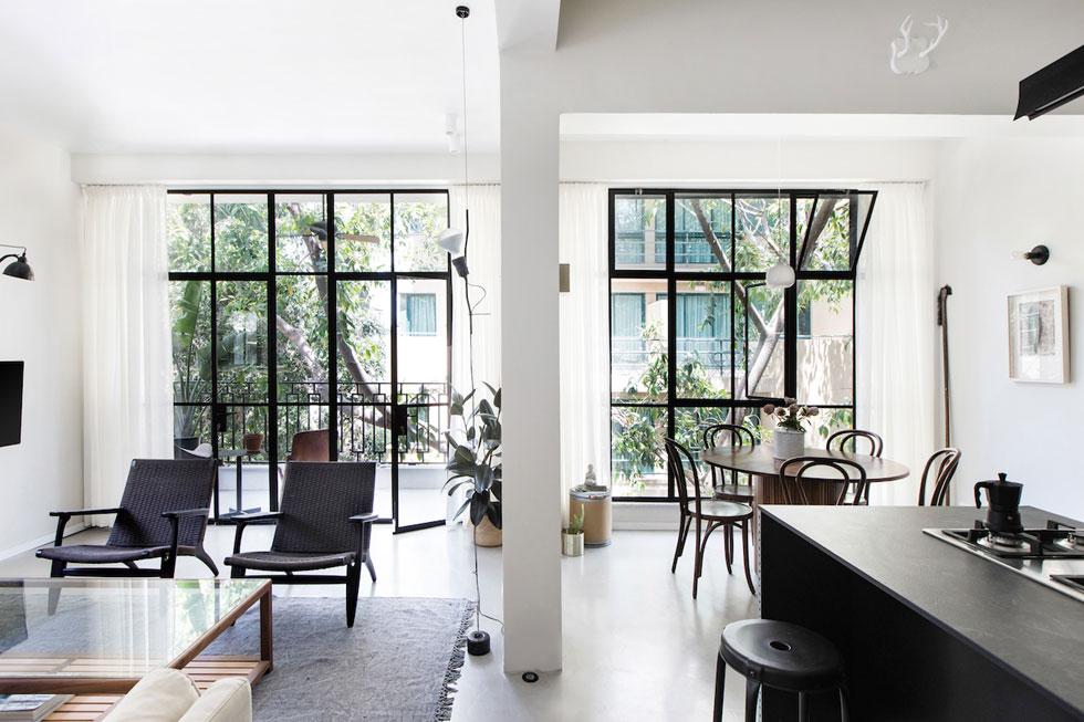 המרחב הפתוח בדירה, ששטחה 76 מ''ר. המרפסת הוקטנה מעט כדי ליצור קיר ויטרינות ישר, שמכניס פנימה הרבה אור, אוויר ואת נוף הפיקוסים (צילום: שירן כרמל)