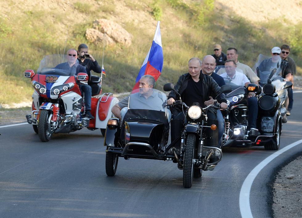 נשיא רוסיה ולדימיר פוטין עם חברי מועדון האופנוענים זאבי הלילה ב חצי האי קרים (צילום: רויטרס)