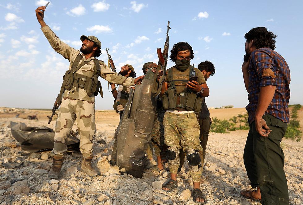המורדים סוריה עם שברי המטוס מטוס אידליב  חאן שייחון   (צילום: AFP)