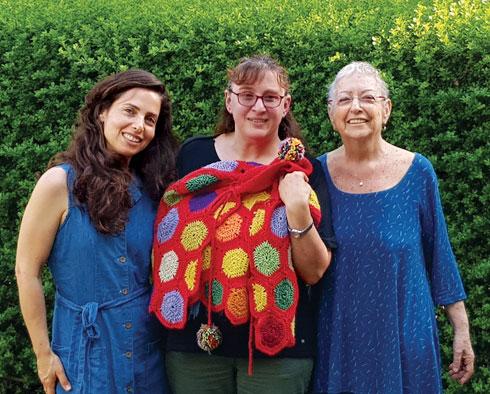 רביד מקבלת את הפונצ'ו מלירון קידר־הלפרין ואמה מלכה (צילום: לירון מילול)