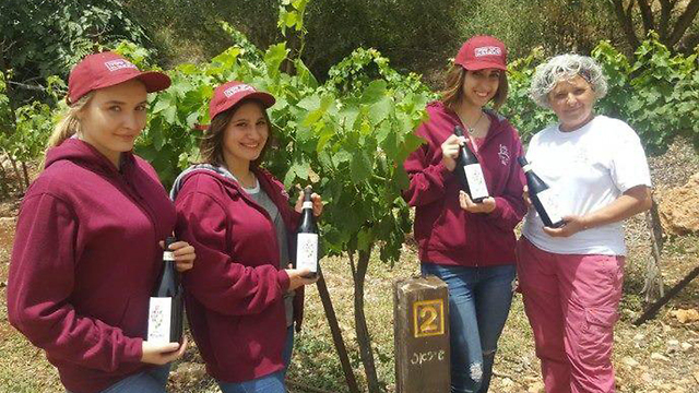 תלמידות מכפר הנוער החקלאי מאיר שפיה מחזיקות ביין שהכינו (באדיבות כפר הנוער מאיר שפיה)