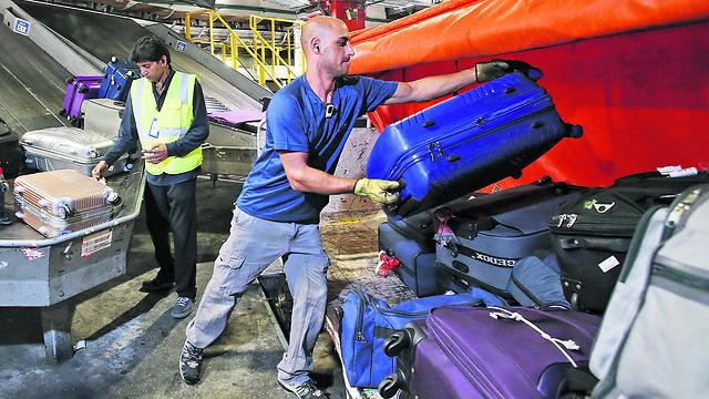 עובד מרים מזוודות (צילום: שאול גולן)
