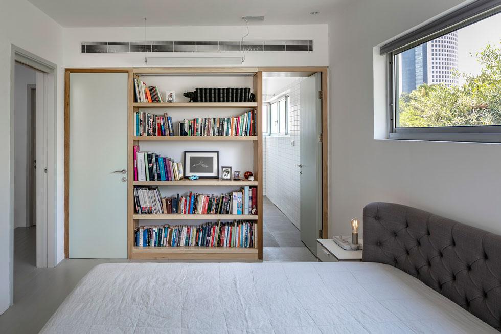 """חדר השינה הראשי. במרכז הקיר שלצד המיטה ספרייה, ומשני צדיה דלתות: הימנית מובילה לחדר הרחצה והשמאלית לחדר ארונות עם מדפים פתוחים. """"זה החדר האהוב עלי"""", אומר כהן, """"אני מגלה דברים שלא זכרתי שיש לי""""  (צילום: עוזי פורת)"""