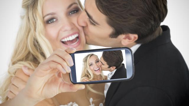 אילוסטרציה של חתן וכלה עושים סלפי (צילום: Shutterstock)