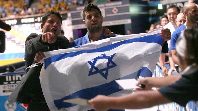 Judoka Sagi Muki and his coach Oren Smadja hold the Israeli flag after his World Championship win (Photo: Oren Aharoni)