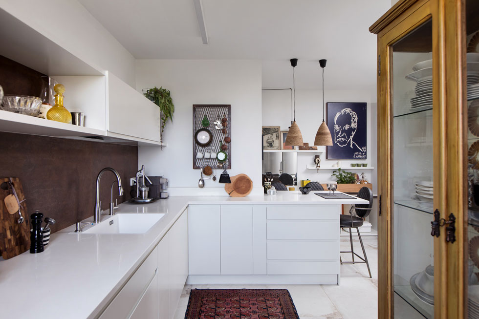 המטבח החדש הוא החלק העכשווי והנקי ביותר בעיצובו, עם ארונות לבנים וחיפוי קיר בגוון חלודה (צילום: שירן כרמל)