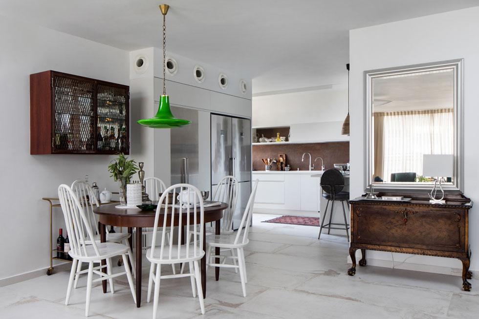 הכניסה לדירה. פינת האוכל ניצבת במקומה המקורי, עם אותו שולחן ואותם כסאות, שרק נצבעו מחדש בלבן. מעל מאירה מנורת זכוכית ירוקה, כמעט זהה למקורית, שנשברה במהלך השיפוץ (צילום: שירן כרמל)