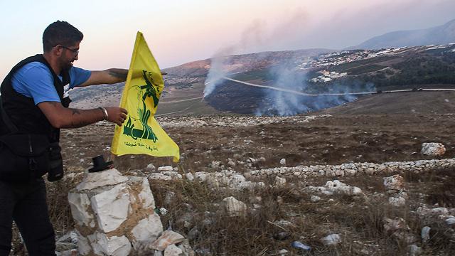 Lebanese residents near the border put up Hezbollah flag (Photo: AFP)