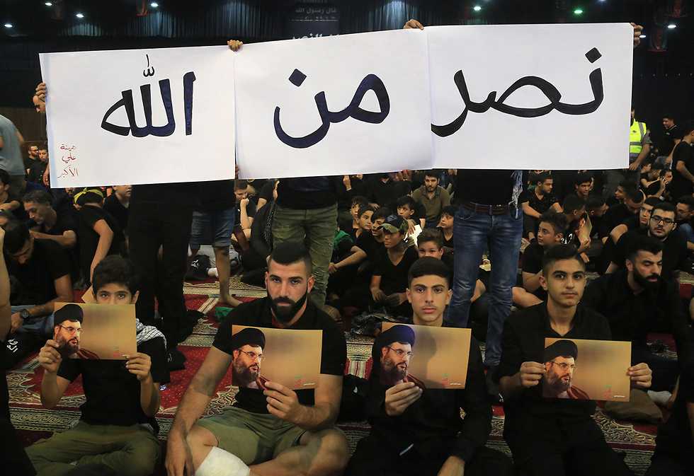 "Hezbollah members carry signs ""Victory is from God"" during Nasrallah's speech Monday (Photo: AFP)"