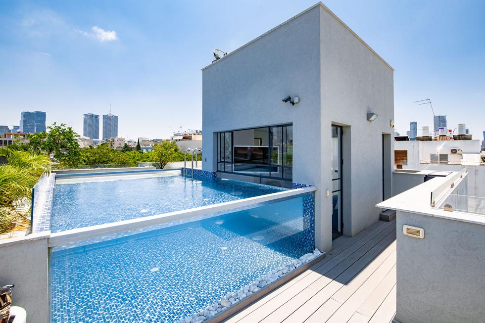 """בריכה עם דפנות זכוכית, בפנטהאוז על גג של בניין מגורים בלב תל אביב. """"השקעה משתלמת"""" (צילום: נופר בוגנים)"""