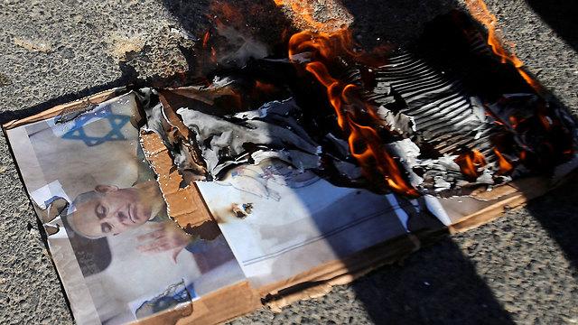 פעילים פלסטינים מציתים את תמונת בנימין נתניהו בחברון (צילום: רויטרס)