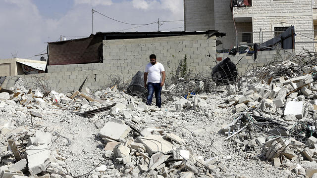 Palestinian Jihad Rajabi walks on the rubble of his house that was demolished by Israeli authorities, in the east Jerusalem neighborhood of Beit Hanina