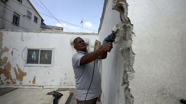 Palestinian Jamil Masalmeh uses a power tool to destroy an apartment he had added to his home years earlier, in the Silwan neighborhood of east Jerusalem
