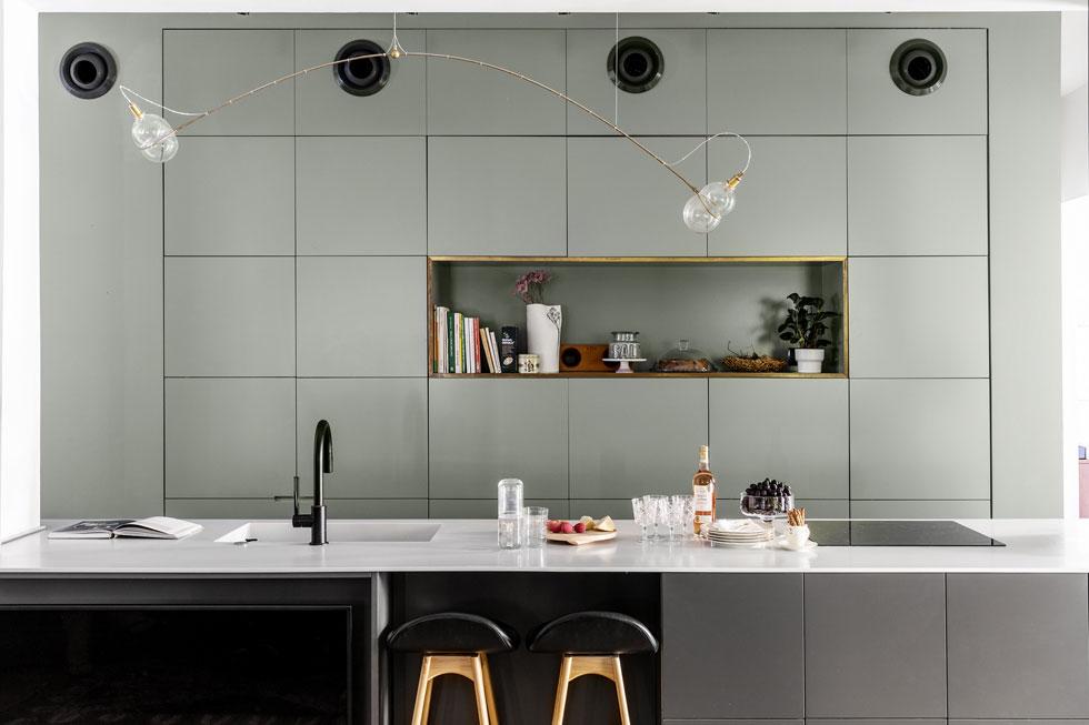 """בקיר הארונות הגבוהים במטבח מוטמע המקרר. באי משולבים תנור, כיריים וכיור. את המנורה מעל עיצב אוהד בנית. """"זו הייתה מתנת יום הולדת לעצמי"""", אומרת גרף-רחים. משמאל, ליד הכסאות, נראה קצה מסך הטלוויזיה המופנה לסלון (צילום: איתי בנית)"""