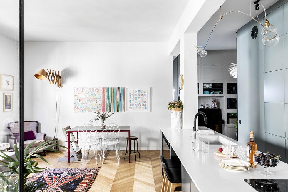 לצד האי רק שני מקומות ישיבה, והארוחות המשפחתיות מתקיימות סביב שולחן האוכל. על הרצפה פרקט בדוגמת שברון, אחד הזכרונות מתקופת לימודיה של רחלי גרף-רחים, בעלת הבית, בפריז. יחד עם האדריכלית אורית זינגר, היא הייתה שותפה לתכנון ולעיצוב הדירה (צילום: איתי בנית)