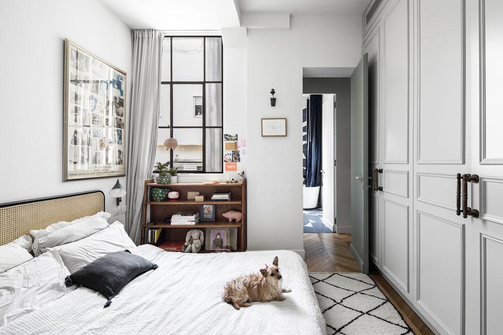 מסדרון מוביל לחדר הרחצה המרכזי ולחדר ההורים. המזרון מונח על הרצפה, וכראש מיטה משמשת מסגרת ראטן התלויה על הקיר (צילום: איתי בנית)