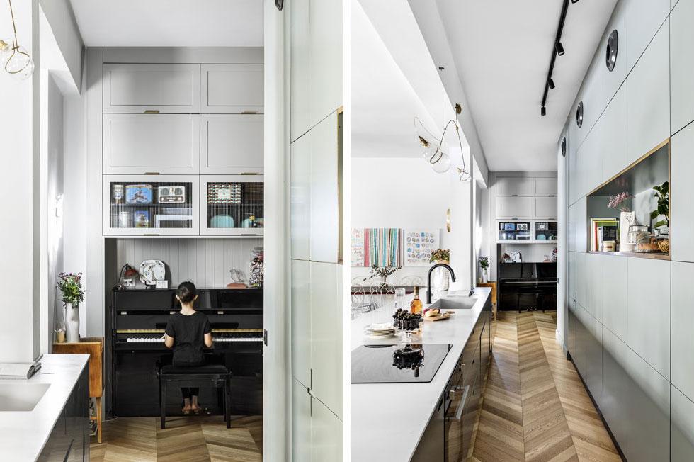 """מבט מצדו השני של המטבח, לכיוון המבואה, שהפכה ל""""חדר נוסף"""" שבו פסנתר, ספרייה ופינת קריאה. במרכז הדירה - האי, וסביבו התנועה בדירה (צילום: איתי בנית)"""