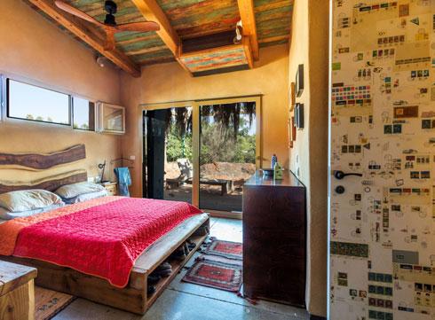 דלת ישנה מכוסה בקולאז' נפתחת אל חדר השינה. גם את המיטה בנו בעצמם (צילום: תלמידי צילום מקצועי, לימודי חוץ, ויצו חיפה)