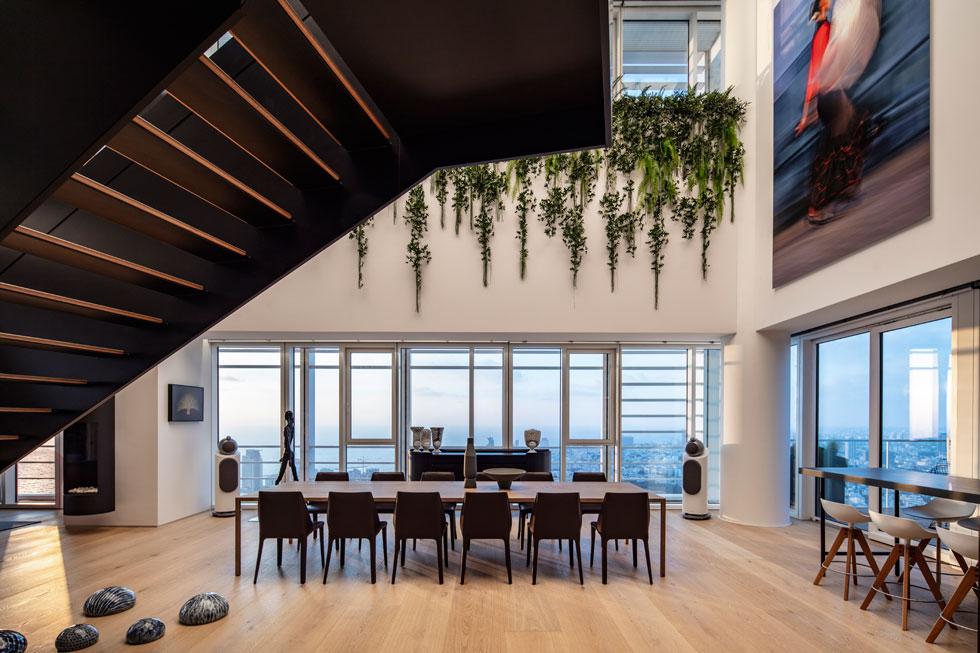 על הקיר הגבוה, שהיה במקור שייך לקומה העליונה, שבוטלה כאן - תכננו האדריכלים לשתול צמחייה אנכית. משהתברר שהתחזוקה תהיה כמעט בלתי אפשרית, הוחלט להסתפק בצמחייה מלאכותית. בעתיד ירחפו מעל המטבח ופינת האוכל ארבעה גופי תאורה רובוטיים, דמויי מנורות הזרוע של ''פיקסאר'' (צילום: עמית גרון)