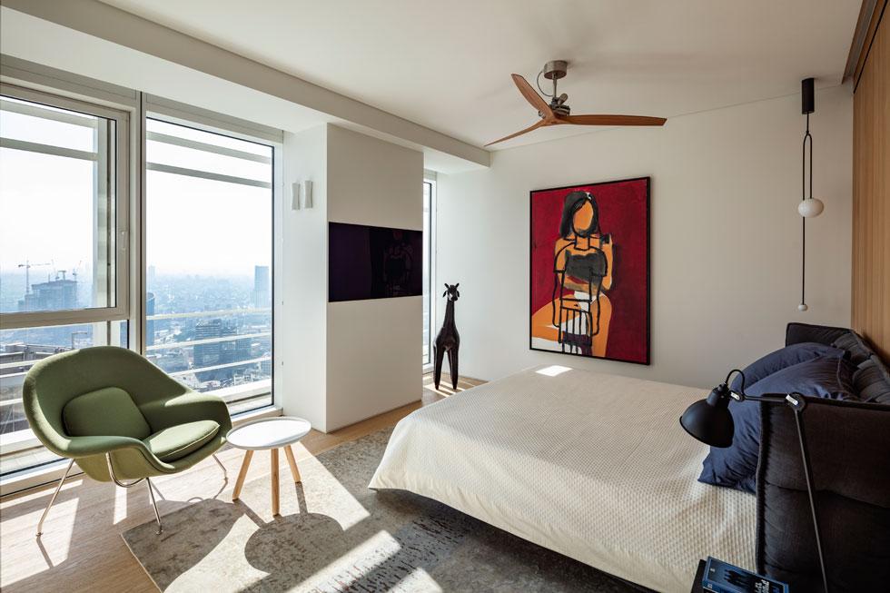 חדר השינה מרוהט בפשטות. המיטה פונה אל הנוף ובגבה קיר מכוסה עץ בהיר, שמאחוריו חדר ארונות רחב-ידיים (צילום: עמית גרון)