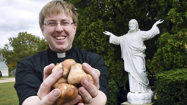The Rev. Andrew K. Nelson of Saint Ignatius of Loyola Parish in Somersworth, N.H. holds tulip bulbs that will be planted to honor Wilhelmina Wiegman