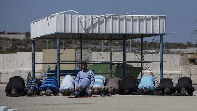 Palestinian workers pray at Erez crossing