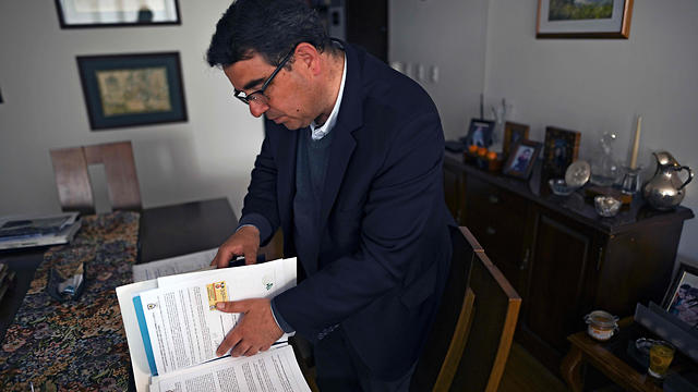 Colombian Andres Villegas -a Catholic who has a Sephardic Jewish ancestor- looks into documents during an interview in Bogota