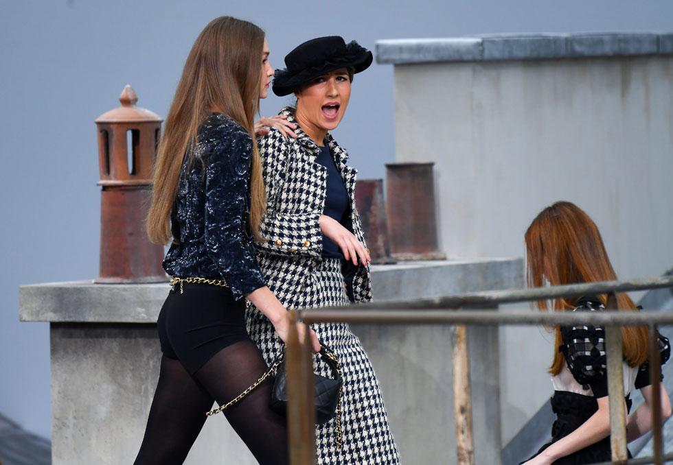 """את השעמום מתצוגת האופנה של שאנל הצילה הקומיקאית הצרפתייה מארי בנולייל, שבזמן הפינאלה קפצה על המסלול לבושה חליפת טוויד וצעדה עם הדוגמניות, עד שנחסמה בגופה על ידי ג'יג'י חדיד שהראתה לה את הדרך החוצה. בענף האופנה מיהרו להכתיר את חדיד כ""""גיבורה"""" ו""""אמיצה"""" (צילום: rex/asap creative)"""