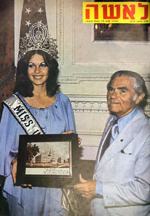 """""""ראש עיריית ניו־יורק אברהם בים, מקבל בלשכתו את פני 'מיס תבל', רינה מור, ומעניק לה את תמונת בית העירייה עם הקדשה בכתב ידו""""  (צילום: AP)"""