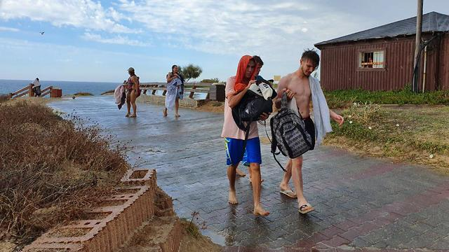 Beachgoers hide from rain in central Israel (Photo: Avigail Uzi)