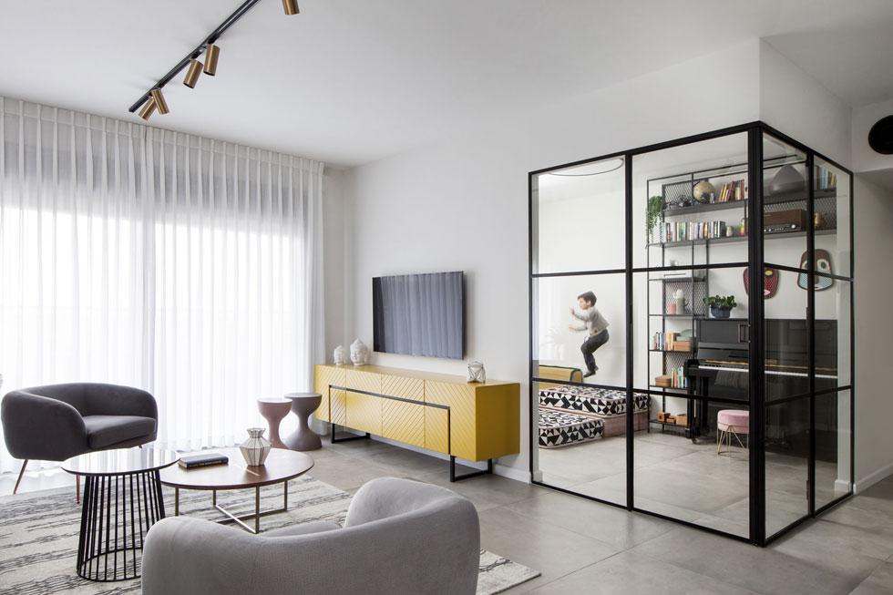 """חדר משחקים, נגינה וצפייה בדירת משפחה בגני תקווה. """"ביום יום"""", אומר המעצב טוביה פנפיל, """"דלתות הזכוכית פתוחות והחדר מתחבר אל הסלון"""" (צילום: שירן כרמל)"""
