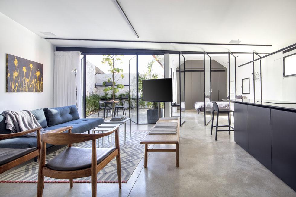 מה עושים כשרוצים לתת לדירה קטנה מראה של לופט מאוורר? בונים קירות שקופים בין המטבח לחדר השינה, ובין הסלון למרפסת. תכנון: רז מלמד (צילום: עמית גרון)