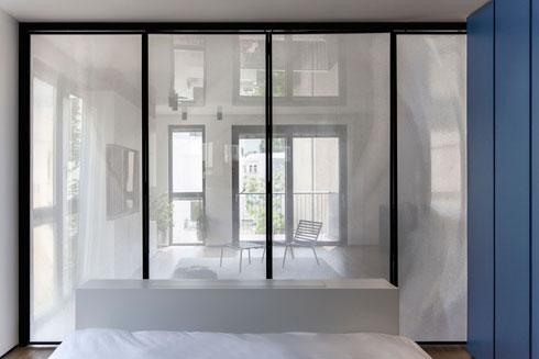 מבט מתוך חדר השינה אל הסלון. במקרה הזה המחיצה אינה עשויה זכוכית, אלא פרספקס עם דוגמה עדינה (צילום: Beller)