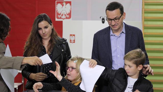 ראש ממשלת פולין מתיאוש מורבייצקי בקלפי עם משפחתו - בדרך לניצחון (צילום: EPA)