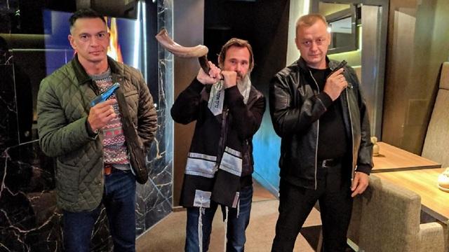 Kirt Schneider and his shofar, his bodyguards and their guns