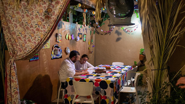 Yoni Stanleigh and his daughter Nehora sit in their sukka (Photo: Reuters)