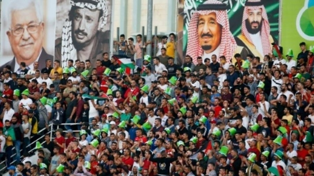 Pictures, from left, of Palestinian President Mahmoud Abbas, the late Palestinian leader Yasser Arafat, Saudi Arabia's King Salman and Crown Prince Mohammad bin Salman, adorn the stadium as fans cheer for their team during a FIFA World Cup Asian Qualifying Group Four soccer match between Palestine and Saudi Arabia, at Faisal Husseini Stadium, in the West Bank, Oct. 15. 2019 (Photo: AFP)