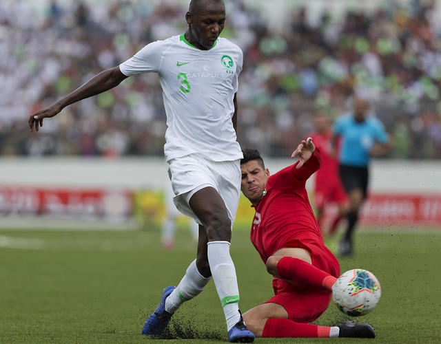 Saudi Arabia's Abdullah Madu, left, passes Palestine's Tamer Seyam during their World Cup qualifyier in the West Bank Oct. 15. 2019