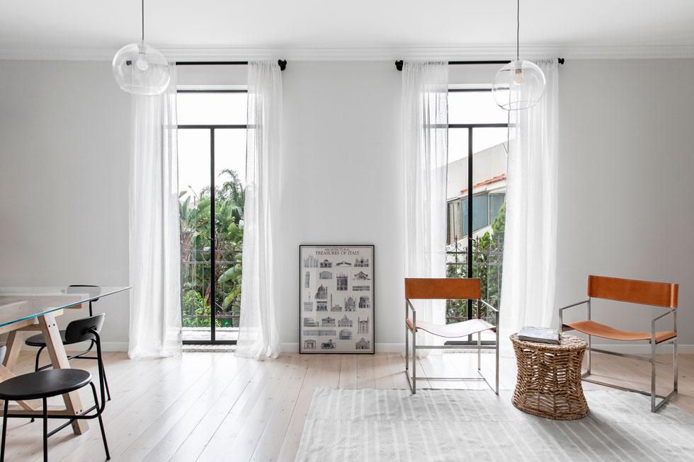 בחדר העבודה, צבע הקירות מתחלף לאפור בהיר, אך הוא ממשיך לשמש מצע לאותם וילונות לבנים ולריהוט קליל בחומרים טבעיים (צילום: איתי בנית)